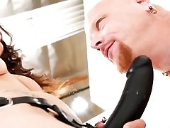 She is dressed in a giant black strap-on and is measuring it to his dick