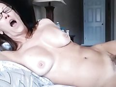 Cougar lady laying on couch uncovering her extremely hairy pussy crevice